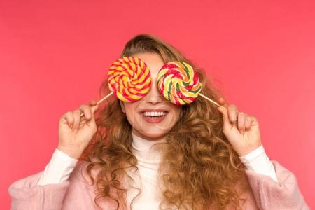 Photo for Happy girl covering eyes with round lollipops isolated on red - Royalty Free Image