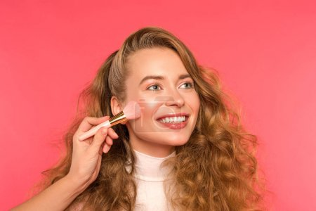 cropped image of woman doing makeup for smiling girl isolated on red