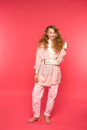 Photo for Stylish girl in pink outfit holding milkshake isolated on red - Royalty Free Image