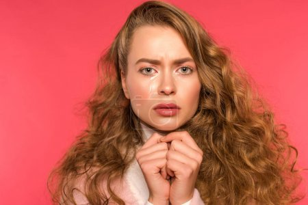 Photo for Upset crying girl looking at camera isolated on red - Royalty Free Image