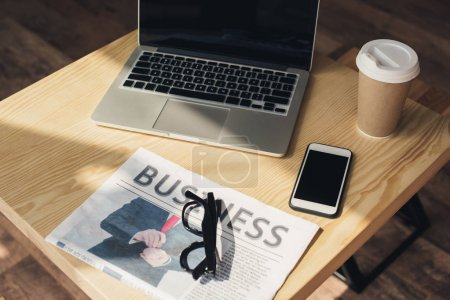 coffee break with laptop, smartphone and business newspaper on table in coffee shop