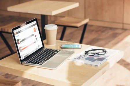 Photo for Laptop with soundcloud, smartphone with uber and business newspaper on table in coffee shop - Royalty Free Image