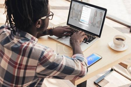 Photo for African american man using laptop with linkedin website and smartphone with shazam appliance - Royalty Free Image