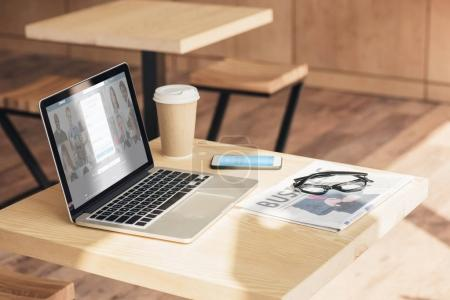 laptop with linkedin website, smartphone with skype and business newspaper on table in coffee shop