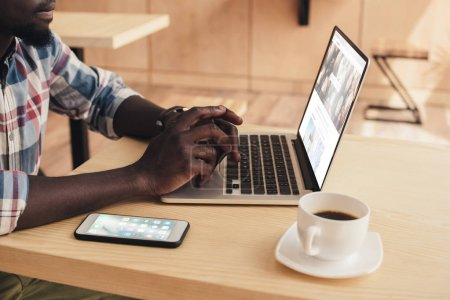 cropped view of african american man using laptop with depositphotos website in coffee shop