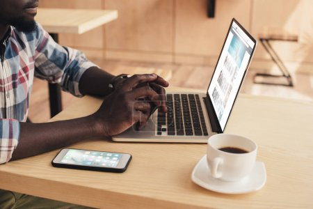 cropped view of african american man using laptop with amazon website and smartphone  in coffee shop