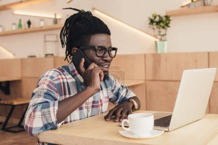 african american man with laptop and cup of coffee talking on smartphone in cafe