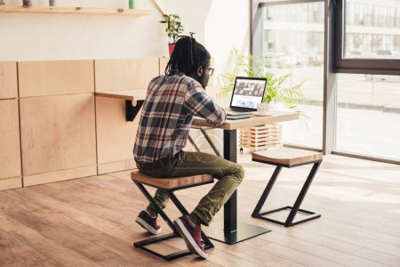 back view of african american man using laptop with depositphotos website in coffee shop