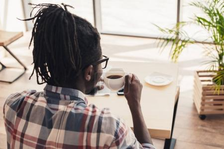 back view of african american man drinking aromatic coffee in cafe