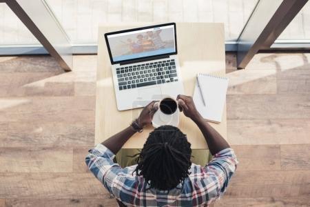 Photo pour Vue aérienne d'afro-américain de boire du café et à l'aide de portable avec le site couchsurfing - image libre de droit