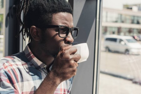 african american man drinking coffee while standing at window