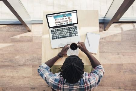 overhead view of african american man drinking coffee and using laptop with amazon website