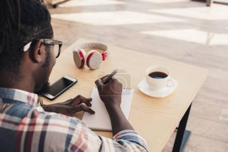 african american man writing in notepad during coffee break in cafe