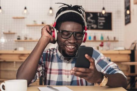 african american man listening music and using smartphone in coffee shop