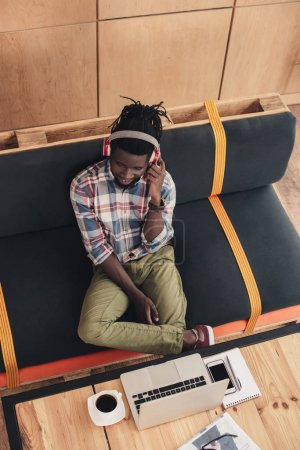 overhead view of african american man listening music with headphones and using gadgets in cafe