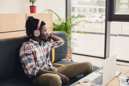 african american man listening music with headphones in coffee shop with laptop