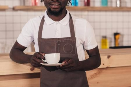 cropped view of african american barista in apron holding coffee cup while standing at bar counter