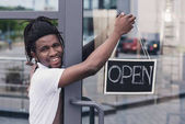 cheerful african american coffee shop owner with open sign