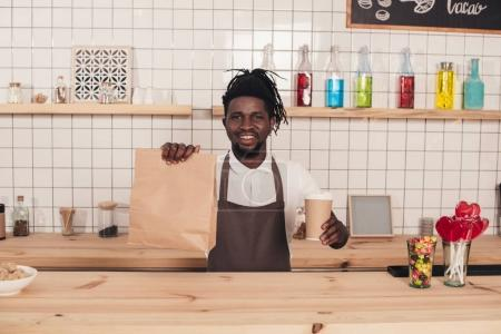 african american barista holding disposable cup of coffee and kraft package at bar counter