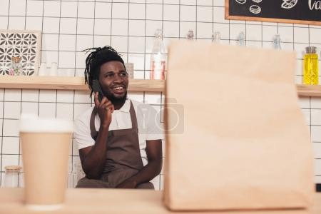 african american barista talking on smartphone, disposable cup of coffee and kraft package standing on foreground on bar counter