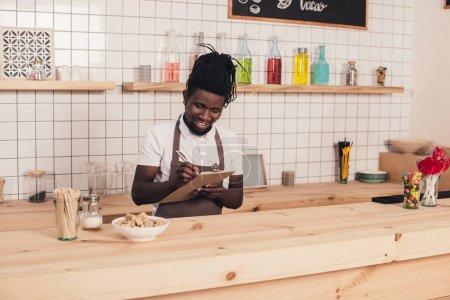 Photo pour Souriant afro-américaine barista prenant commande au comptoir - image libre de droit