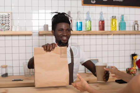 smiling african american barista giving disposable cup of coffee and kraft package to client