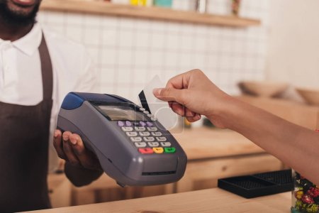 cropped view of client paying with credit card and terminal in cafe