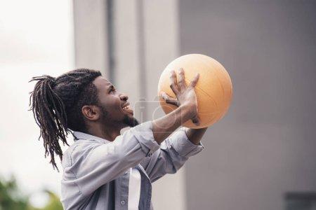 african american man throwing basketball ball at street
