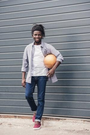 handsome smiling african american man with basketball ball at street