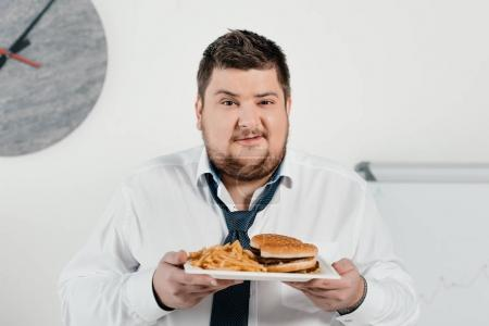 overweight businessman with hamburger and french fries in office
