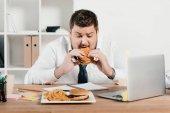 """Постер, картина, фотообои """"избыточный вес бизнесмен, едят нездоровую пищу в офисе"""""""