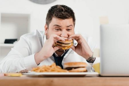 Photo for Overweight businessman eating hamburger and french fries in office - Royalty Free Image
