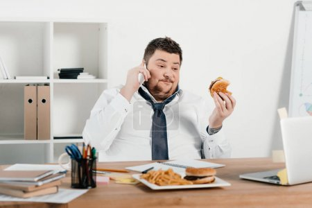 overweight businessman talking on smartphone while eating fast food in office