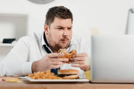 overweight businessman working while eating hamburger and french fries in office