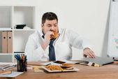 """Постер, картина, фотообои """"избыточный вес бизнесмен ест гамбургер и использовать ноутбук в офисе"""""""