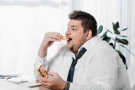 overweight businessman eating hamburger and french fries at workplace