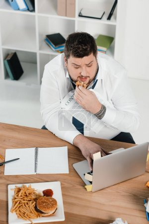 overweight businessman eating junk food while working with laptop in office