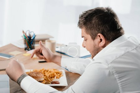 overweight businessman having lunch with hamburger and french fries in office