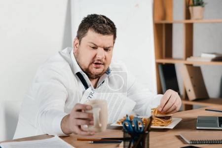 overweight businessman eating fast food and drinking coffee in office
