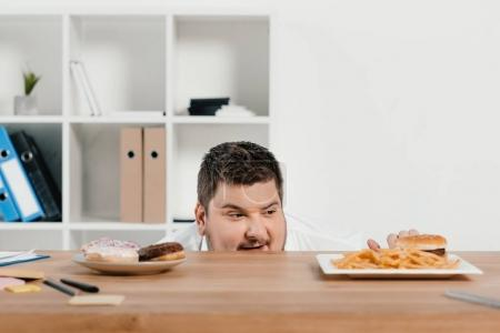 hungry fat businessman choosing donuts or hamburger with french fries for lunch