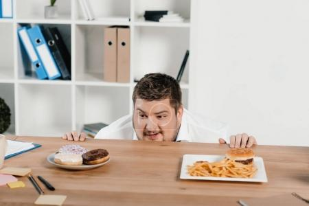 fat businessman choosing donuts or hamburger with french fries for lunch