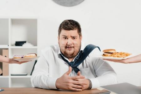 overweight businessman choosing junk food for lunch
