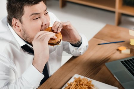 overweight businessman eating hamburger at workplace
