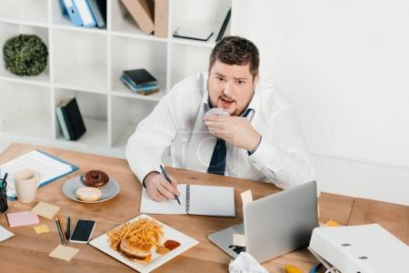 overweight businessman eating donuts, hamburger and french fries while wokring in office