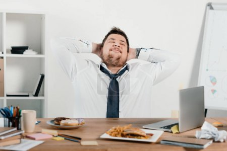 overweight businessman relaxing at workplace with laptop and junk food