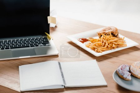 laptop, notepad, donuts and hamburger with french fries at workplace