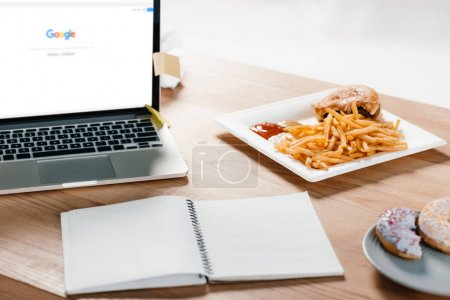 laptop with google website, notepad, donuts and hamburger with french fries at workplace