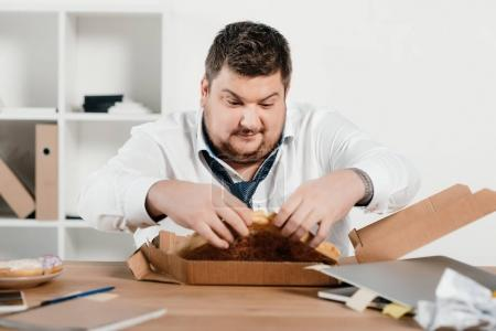 fat businessman eating pizza for lunch at workplace