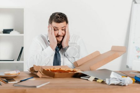 overweight surprised businessman with pizza at workplace