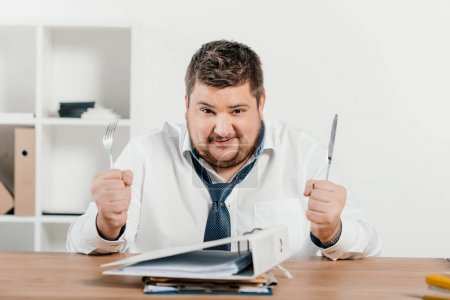 overweight businessman with fork and knife sitting at table with folders
